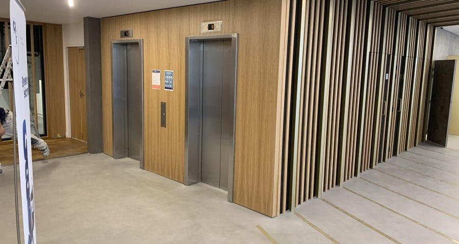 Photo d'un palier d'ascenseurs de l'immeuble Seine Etoile à Suresnes (Société de La Tour Eiffel).